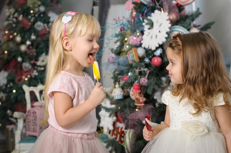Two cute little girls in a festive New Year`s atmosphere with colored lollipops royalty free stock photo