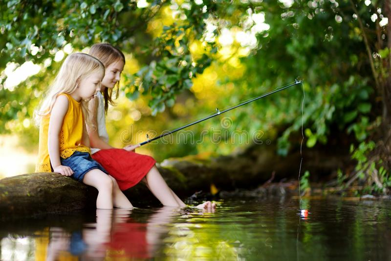 Two cute little girls having fun by a river at beautiful summer evening. Sisters fishing with a fishing rod on warm and sunny day stock photography