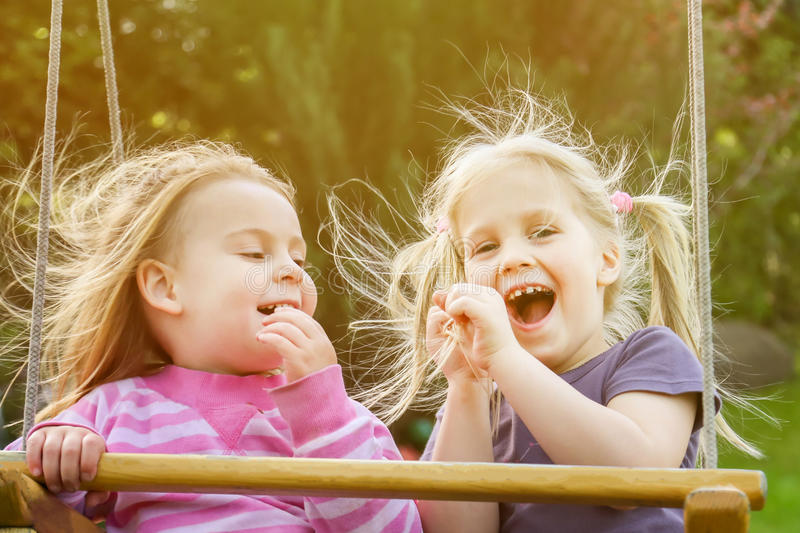 Two cute little girls having fun on a swing together in beautiful summer garden, close-up portrait, soft focus. stock images