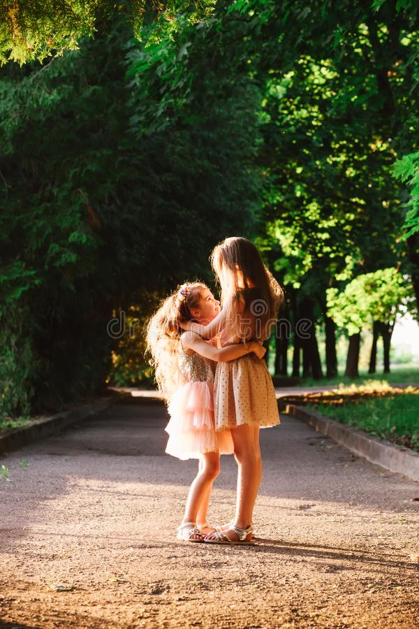Two Cute little girls hugging and laughing at the garden at warm summer evening. Happy kids outdoors concept. Soft focused stock image