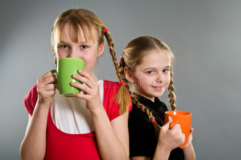 Two cute little girls with mugs stock image