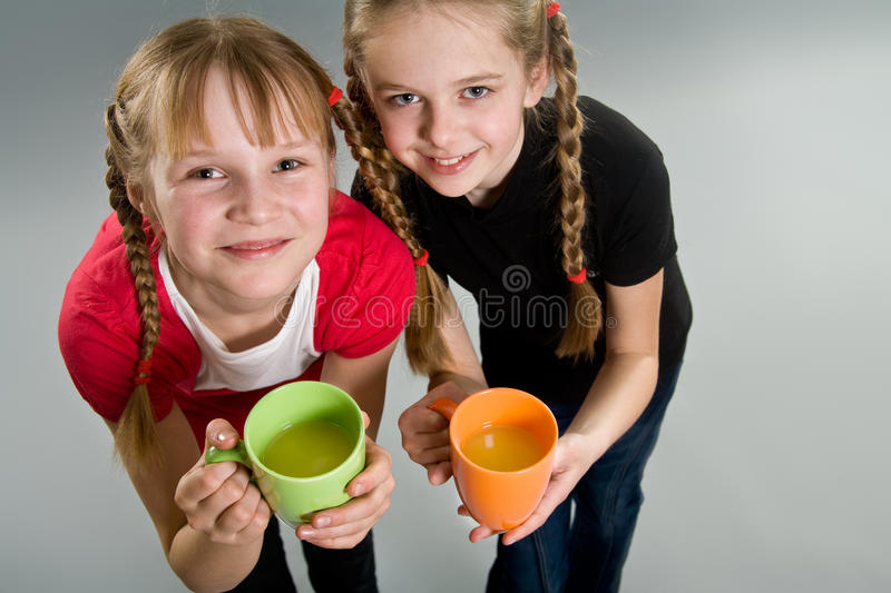 Two cute little girls with mugs stock photo