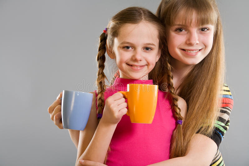 Two cute little girls with mugs royalty free stock photo