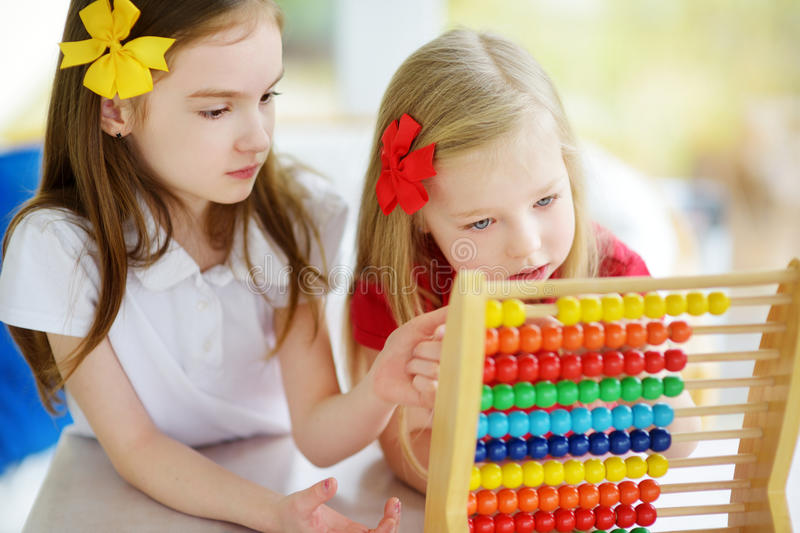 Two cute little girls playing with abacus at home. Big sister teaching her sibling to count. stock images