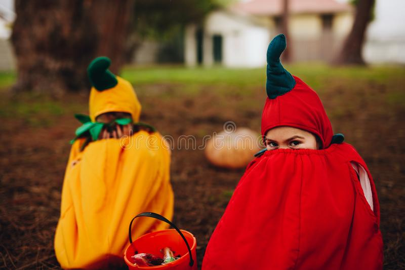 Twin sisters tricking outdoors on halloween stock photo