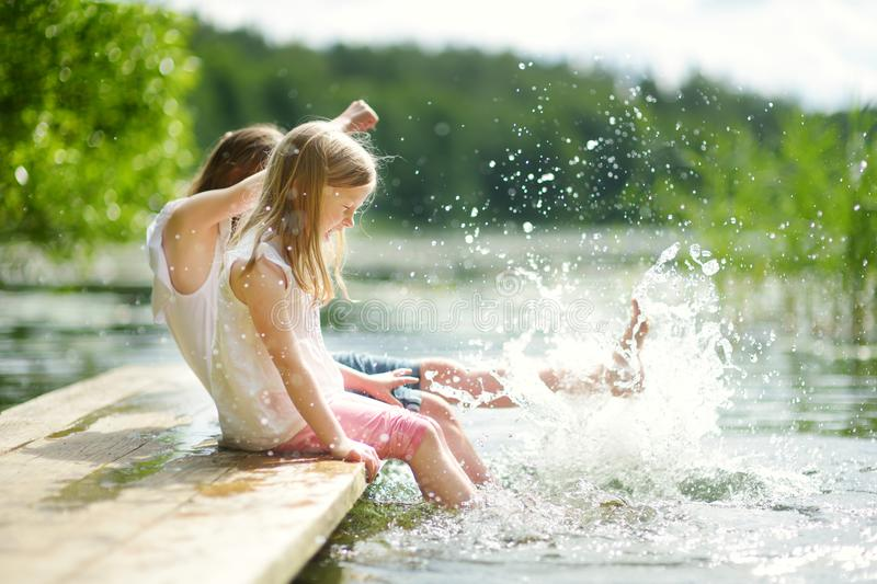 Two cute little girls sitting on a wooden platform by the river or lake dipping their feet in the water on warm summer day. Family activities in summer stock photo