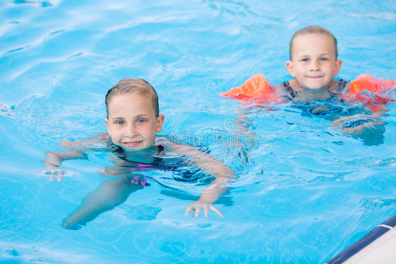 Two cute little girls in swimming pool. Posing stock photo