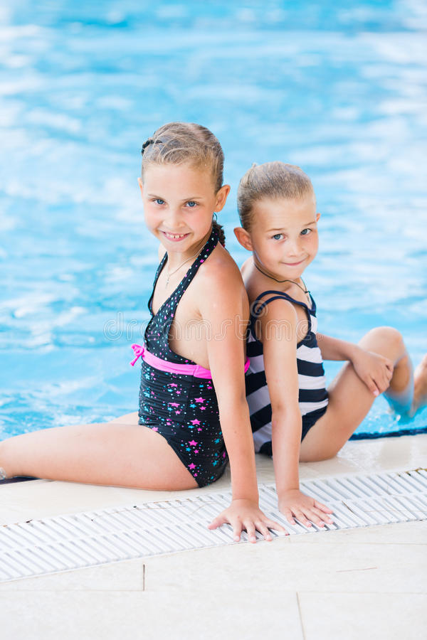 Two cute little girls in swimming pool. Posing stock photography