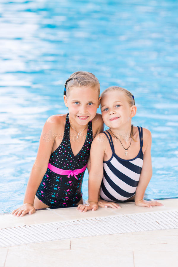 Two cute little girls in swimming pool. Posing royalty free stock image
