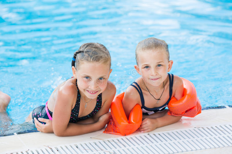 Two cute little girls in swimming pool. Posing royalty free stock photos