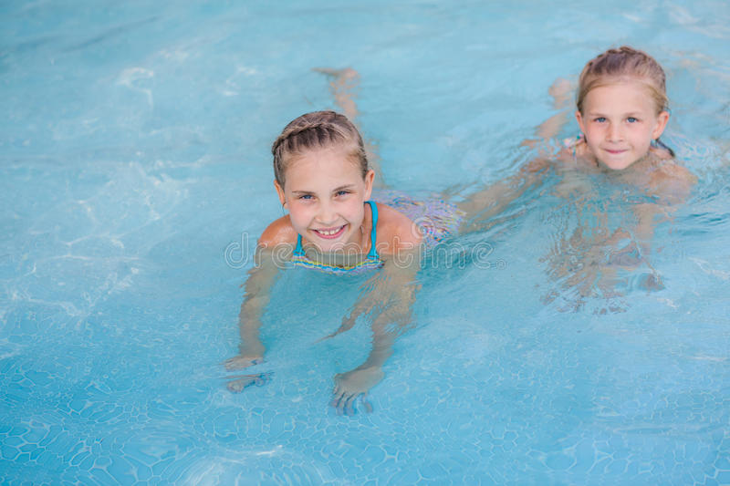Two cute little girls in swimming pool. Posing royalty free stock photo