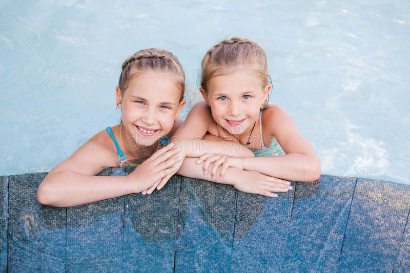 Two cute little girls in swimming pool. Posing stock image