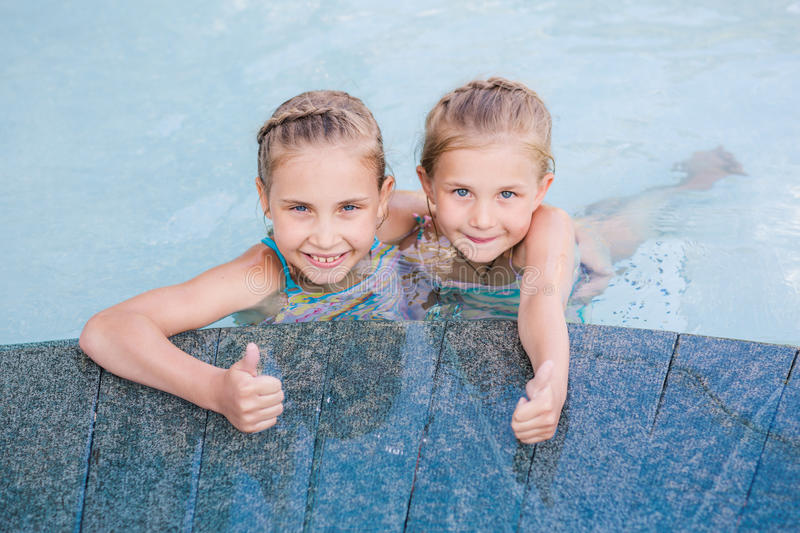 Two cute little girls in swimming pool. With thumbs up royalty free stock photos