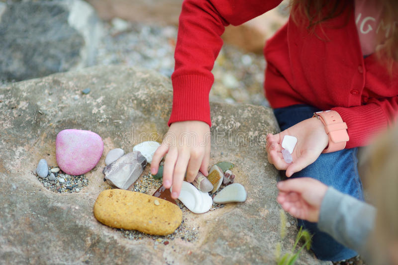 Two cute little sisters collecting beautiful stones on a pebble beach royalty free stock image