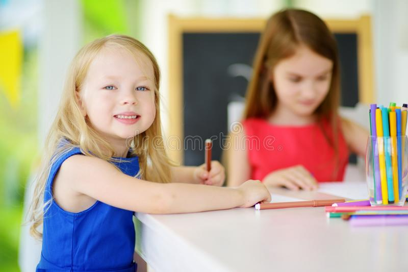 Two cute little sisters drawing with colorful pencils at a daycare. Creative kids painting together. Girls doing homework at home royalty free stock image