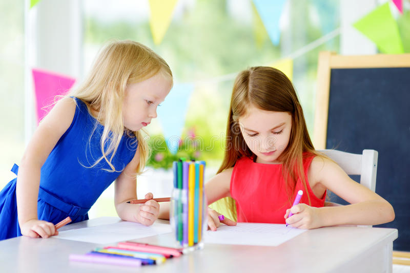 Two cute little sisters drawing with colorful pencils at a daycare. Creative kids painting together. Girls doing homework at home royalty free stock photos