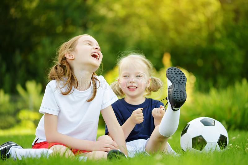 Two cute little sisters having fun playing a soccer game on sunny summer day. Sport activities for children stock photo