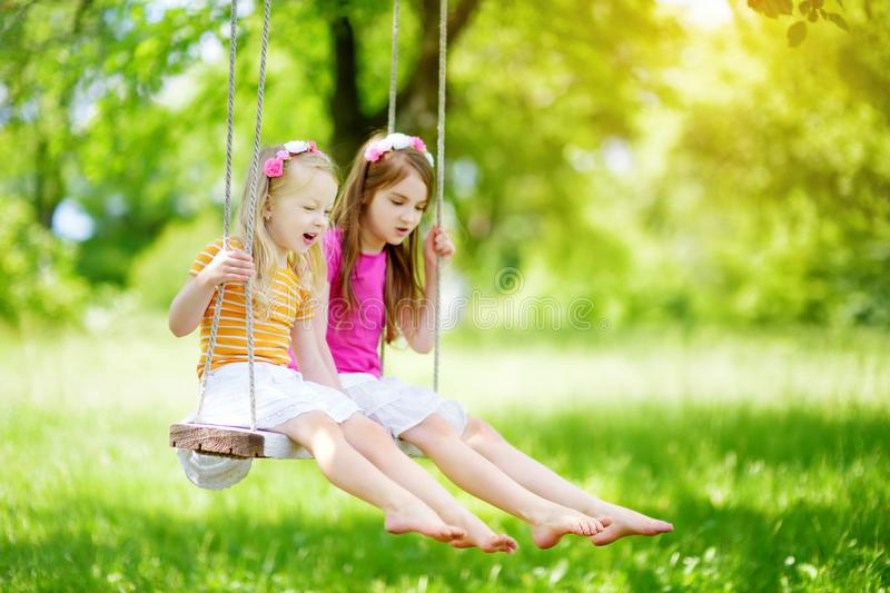 Two cute little sisters having fun on a swing together in beautiful summer garden on warm and sunny day outdoors stock image