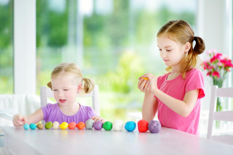 Two cute little sisters having fun together with colorful modeling clay at a daycare. Creative kids molding at home. Children play with plasticine or dough royalty free stock photos