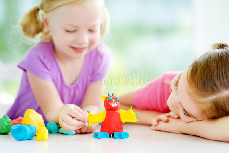 Two cute little sisters having fun together with colorful modeling clay at a daycare stock photography