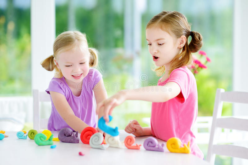 Two cute little sisters having fun together with modeling clay at a daycare. Creative kids molding at home. Children play with pla stock images