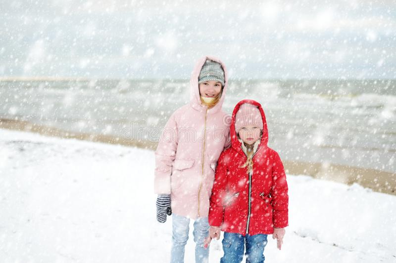 Two cute little sisters having fun together at winter beach on cold winter day. Kids playing by the ocean stock photography