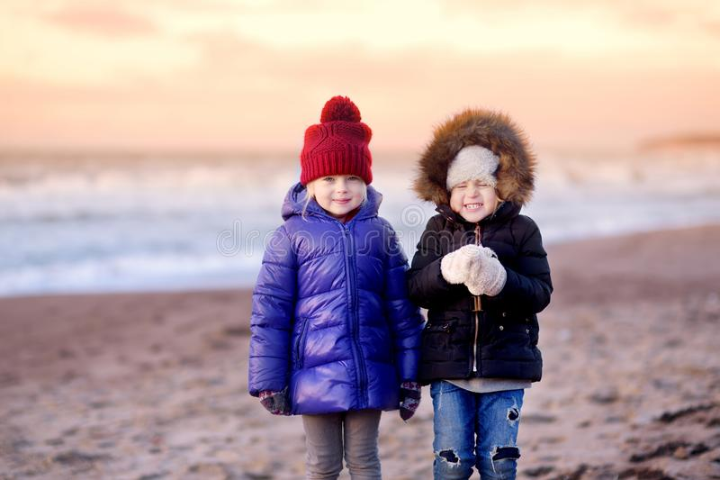 Two cute little sisters having fun together at winter beach on cold winter day. Kids playing by the ocean. royalty free stock photo