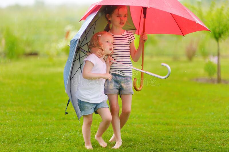 Two cute little sisters holding umbrellas on a rainy summer day royalty free stock photography