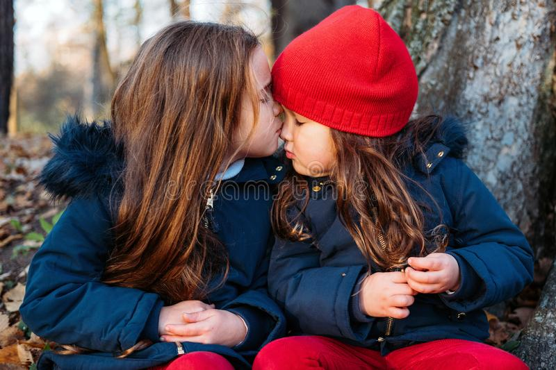 Two cute little sisters kissing. Children hugging and having fun in autumn park. Authentic family moments stock photo