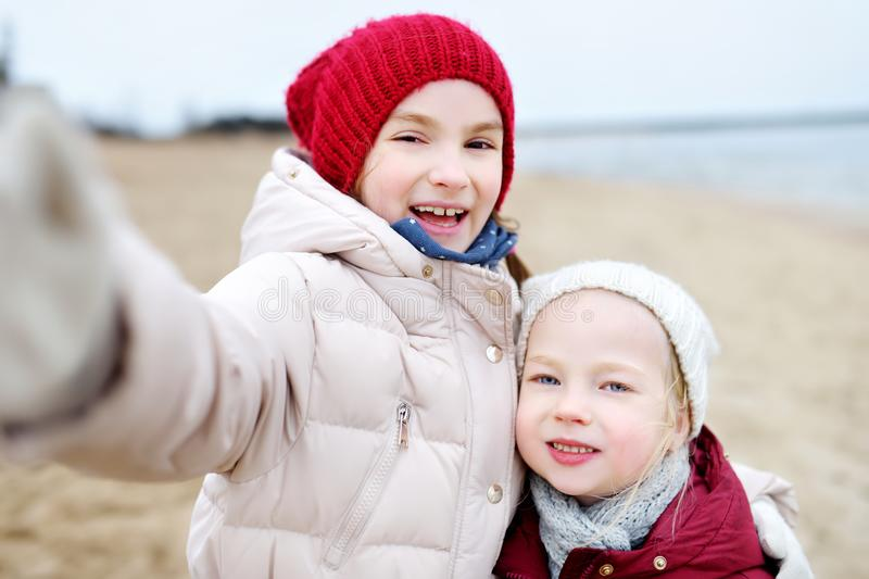 Two cute little sisters taking a picture of themselves at winter beach on cold winter day. Kids playing by the ocean. stock photography