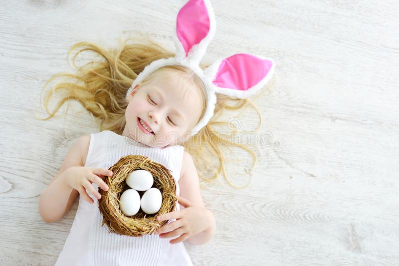 Two cute little sisters wearing bunny ears playing egg hunt on Easter. Adorable children celebrate Easter at home royalty free stock photos