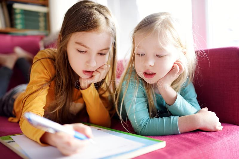 Two cute little sisters writing a letter together at home. Older sister helping youngster with her homework. stock photo