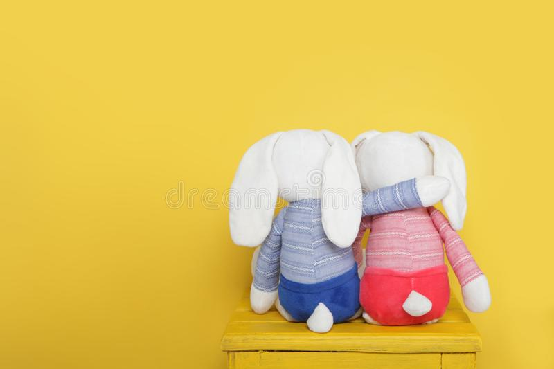 Two cute plush bunnies on yellow background.Rear view stock photos