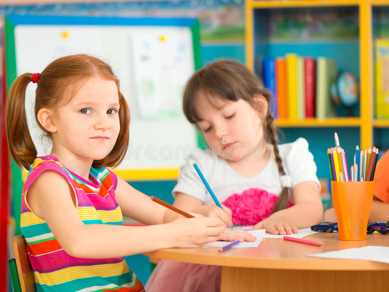 Two cute preschool girls at drawing lesson stock photo
