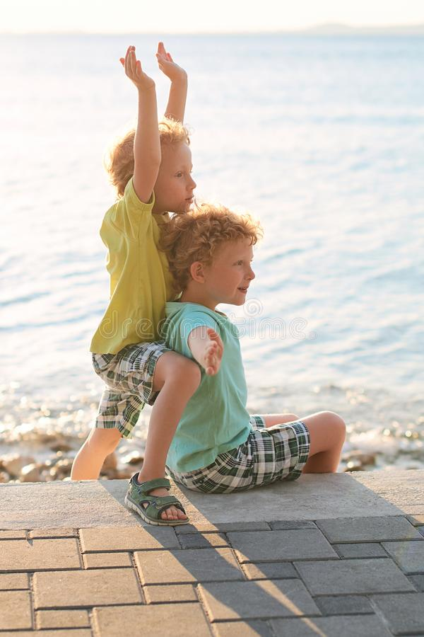 Two cute red curly boys brothers play pretend as they are flying. Or form a robot royalty free stock photo