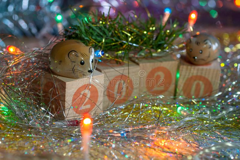 Two cute selenite symbols of new year rat/mouse on the wooden cubes with the numbers 2020 drawn. The silver tinsel, the garland and the fir branch. New year/ royalty free stock image