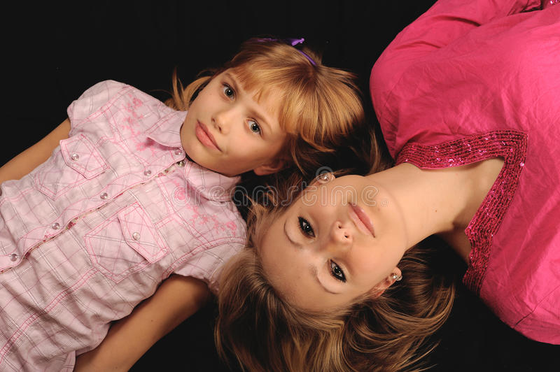 Two cute sisters. Overhead view of two cute sisters lying in opposite directions, black background stock photo