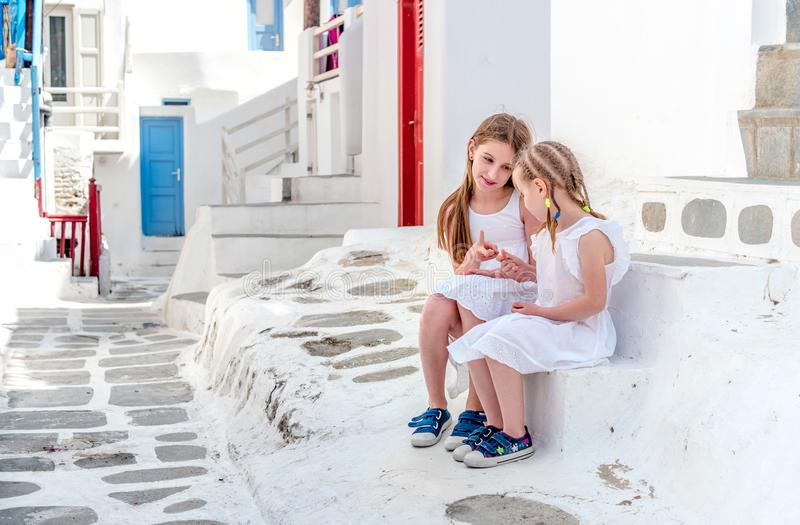 Two sisters sitting on the stairs on the Greek street royalty free stock photo
