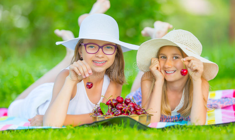 Two cute sisters or friends in a picnic garden lie on a deck and eat freshly picked cherries stock photo
