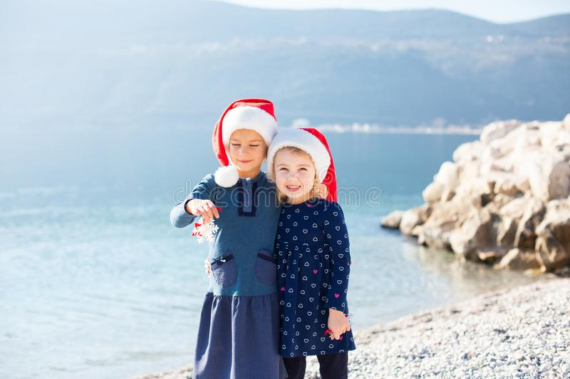 Two cute sisters have winter and New Year vacations in warm destinations. Children emotions outdoors royalty free stock photo