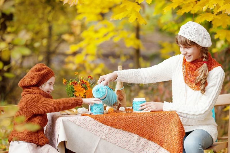 Two cute sisters  on picnic in autumn park. Adorable little girls  having tea party outside in the autumn garden.  Girls drinking stock images