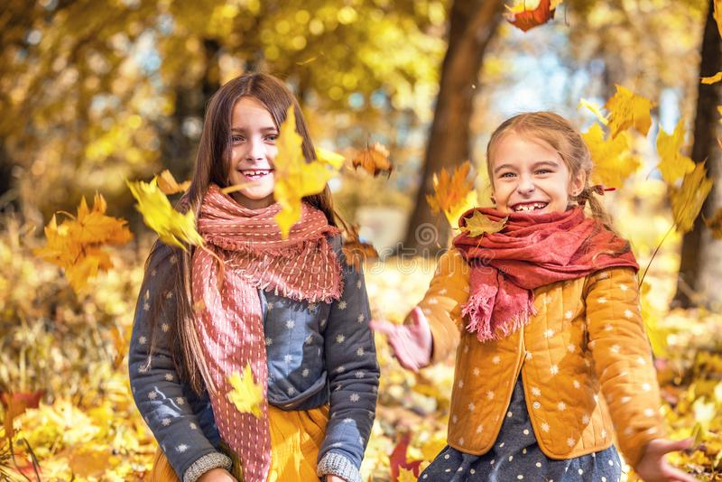 Two cute smiling 8 years old girls playing with leaves in a park on a sunny autumn day. stock photography