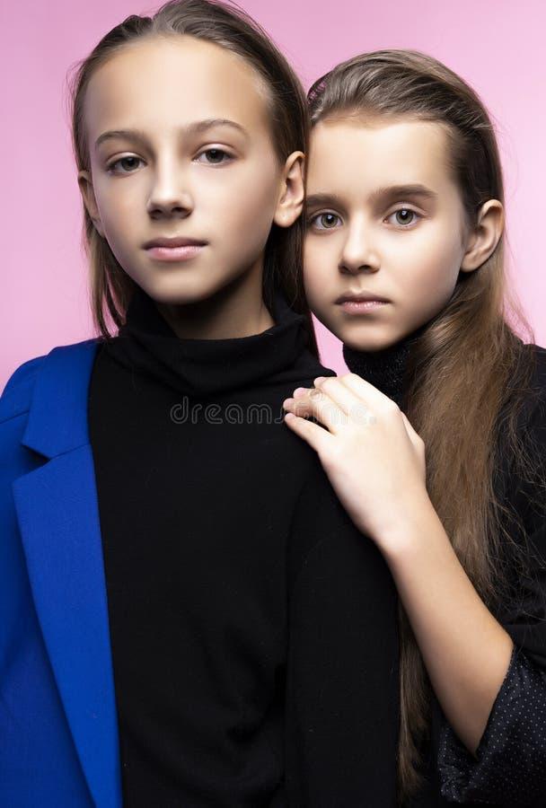 Two cute teenage girlfriends schoolgirls wearing trendy turtleneck sweaters, jeans and blue blazer, hug friendly and posing on royalty free stock image