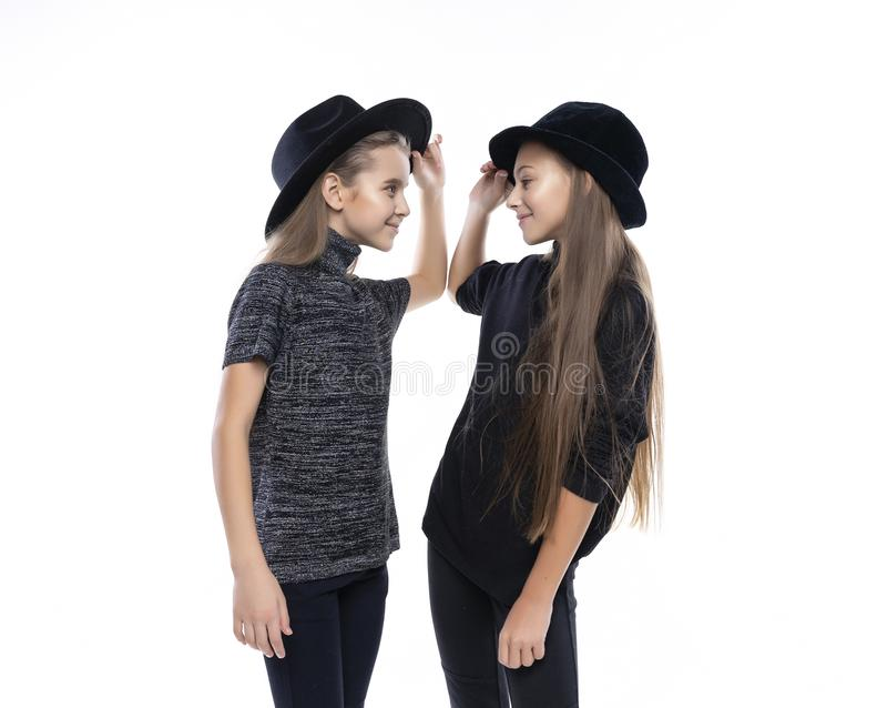 Two cute teenage girlfriends schoolgirls wearing turtleneck sweaters, jeans and hats, smiling dancing and look on each other. stock photo