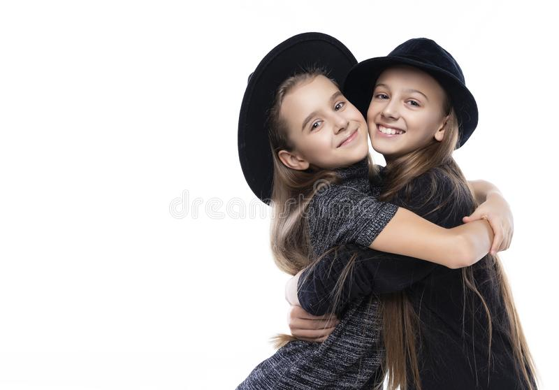 Two cute teenage girlfriends schoolgirls wearing turtleneck sweaters, jeans and hats, smiling hug each other. Isolated on white. royalty free stock photos