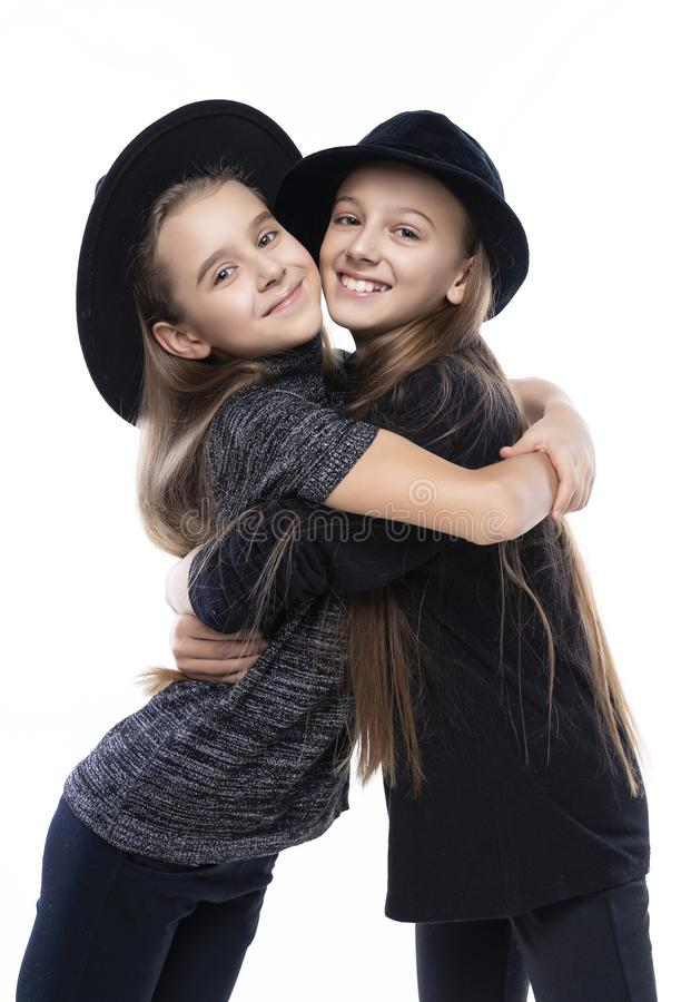 Two cute teenage girlfriends schoolgirls wearing turtleneck sweaters, jeans and hats, smiling hug each other.  on white. royalty free stock photo