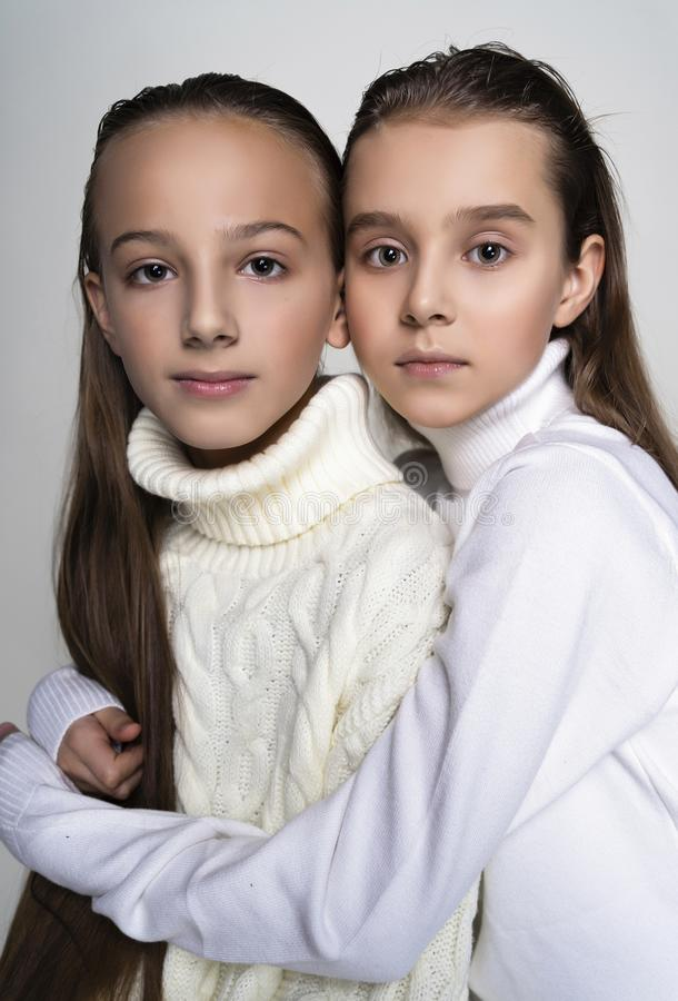 Two cute teenage girlfriends schoolgirls wearing white turtleneck sweaters, sit, hugging each other in a friendly way.  on stock photography