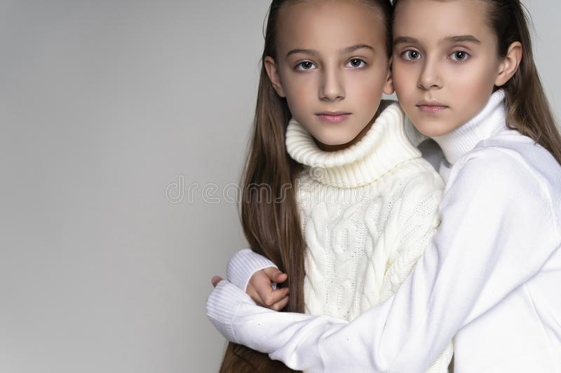 Two cute teenage girlfriends schoolgirls wearing white turtleneck sweaters, sit, hugging each other in a friendly way. Isolated on stock photography