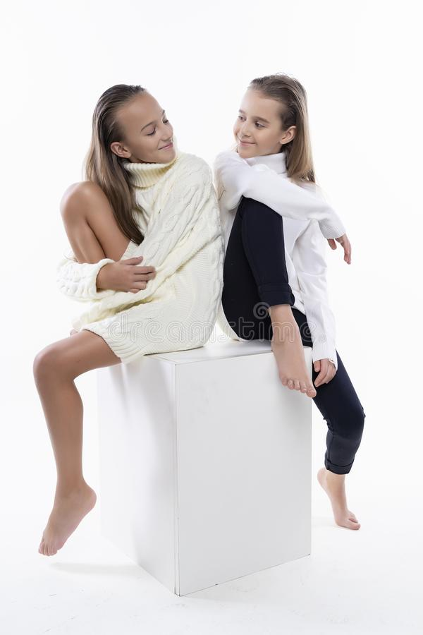 Two cute teenage girlfriends schoolgirls wearing white turtleneck sweaters, smiling sit back to back.  on white. Fashion royalty free stock photos