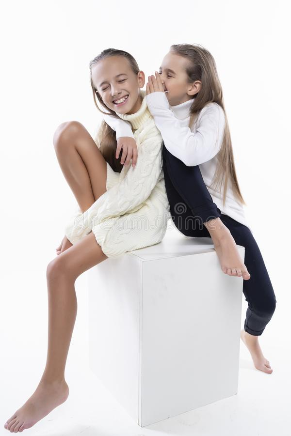 Two cute teenage girlfriends schoolgirls wearing white turtleneck sweaters, smiling sit back to back.  on white. Fashion a stock photos